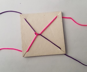 Photo of a square piece of card with a small slit diagonally at each corner. Each slit holds in place one end of a piece of string. There is a tangle of string in the middle of the square.